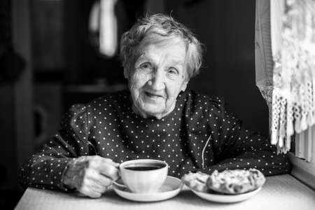 Elderly woman drinking tea with scones. Black-and-white portrait in the interior.