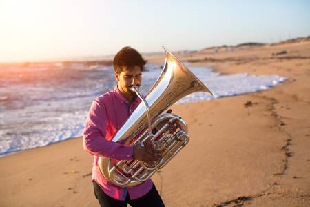 Musician playing the Tuba on the sea coast.