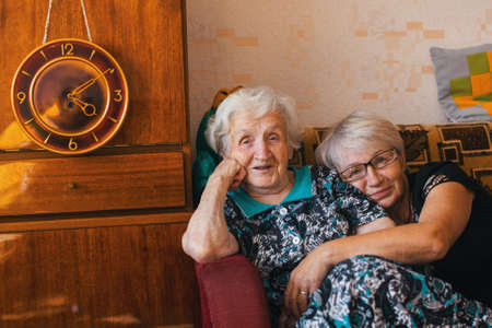 family sofa: An elderly woman with her adult daughter sitting in an embrace on the couch. Stock Photo