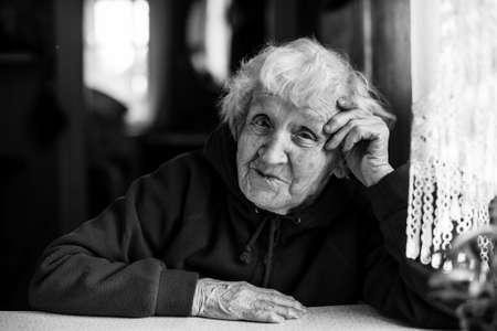 Oudere vrouw aan de tafel zitten. Zwart en wit portret. Stockfoto