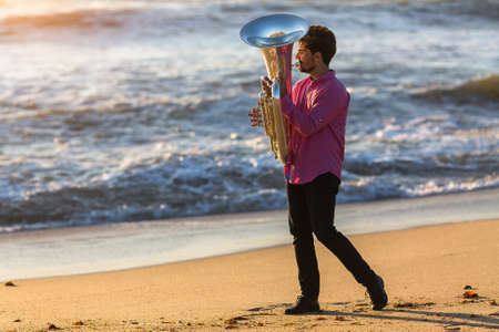 Musician play Tuba on sea beach.
