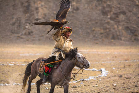 BAYAN-ULGII, MONGOLIA - SEP 30, 2017: Kazakh Eagle Hunter traditional clothing, while hunting to the hare holding a golden eagle on his arm in desert mountain of Western Mongolia. Editorial