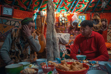 BAYAN-OLGII, MONGOLIA - SEP 28, 2017: Kazakhs family of hunters with hunting golden eagles inside their the mongolian Yurts. In Bayan-Olgii Province is populated to 88,7% by Kazakhs. Stok Fotoğraf - 87504926