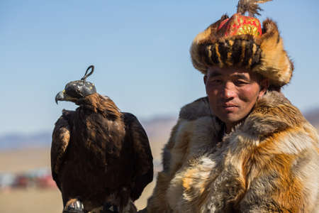 BAYAN-ULGII, MONGOLIA - SEP 30, 2017: Mongolian Kazakh Eagle Hunter traditional clothing, holding a golden eagle on his arm in desert mountain of Western Mongolia. Stok Fotoğraf - 88010107
