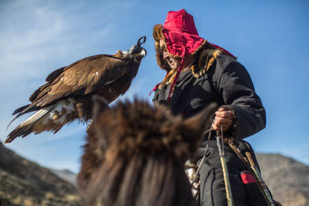 BAYAN-ULGII, MONGOLIA - SEP 30, 2017: Kazakh Eagle Hunter traditional clothing, while hunting to the hare holding a golden eagle on his arm in desert mountain of Western Mongolia. Stok Fotoğraf - 88662702
