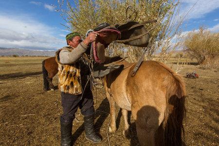 BAYAN-OLGII, MONGOLIA - SEP 28, 2017: Kazakh Berkutchi (Eagle hunter) do saddles horse. In Bayan-Olgii Province is populated to 88,7% by Kazakhs.