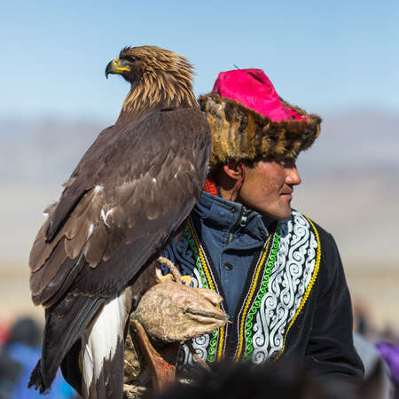 kyrgyzstan: OLGIY, MONGOLIA - SEP 30, 2017: Kazakh Golden Eagle Hunter at traditional clothing, with a golden eagle on his arm during annual national competition with birds of prey Berkutchi of West Mongolia.