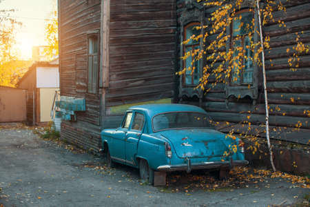 Old vintage car near the wooden urban city. Stock Photo