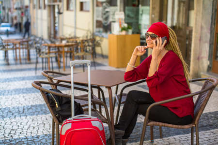 carretilla de mano: A young woman with a red suitcase sitting in a street cafe talking on the phone.
