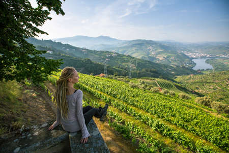Young beautiful woman with blond dreadlocks meets sunset on the viewing point of Douro Valley, Portugal. Top view of river, and the vineyards are on a hills.