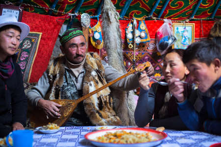 BAYAN-OLGII, MONGOLIA - SEP 28, 2017: Kazakh family of hunters with hunting birds (golden eagles) inside the mongolian Yurt. In Bayan-Olgii Province is populated mainly by Kazakhs (88,7 %) Stok Fotoğraf - 89299692
