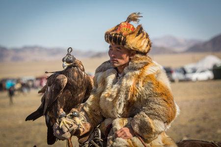 OLGIY、モンゴル - SEP 30 2017: カザフ ゴールデン イーグル ハンター獲物の鳥西のモンゴルのBerkutchiと毎年恒例の全国大会中の伝統的な服で。