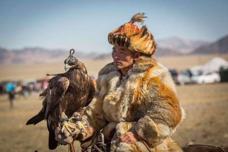 OLGIY, MONGOLIA - SEP 30, 2017: Kazakh Golden Eagle Hunter at traditional clothing, during annual national competition with birds of prey Berkutchi of West Mongolia.