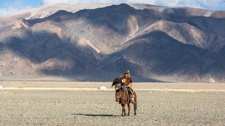 バヤン ・ ULGIY、モンゴル-SEP 27 2017: カザフ イーグル ハンター腕で砂漠山の西モンゴルに金色の鷲を保持しているウサギを狩りながら馬に乗っての伝