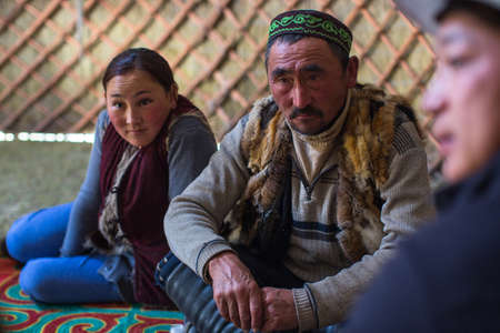 SAGSAI, BAYAN-OLGIY, MONGOLIA - SEP 28, 2017: Kazakh family of hunters with golden eagles inside the mongolian Yurt. In Bayan-Olgii Province is populated mainly by Kazakhs (88,7%) Editöryel