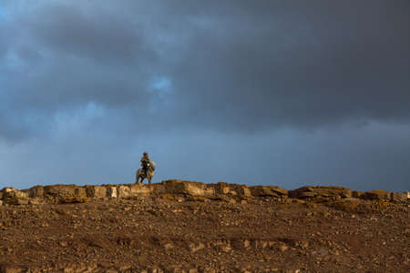 SAGSAY, MONGOLIA - SEP 28, 2017: Golden Eagle Hunter, while hunting to the hare holding a golden eagles on his arms in desert mountain of Western Mongolia.