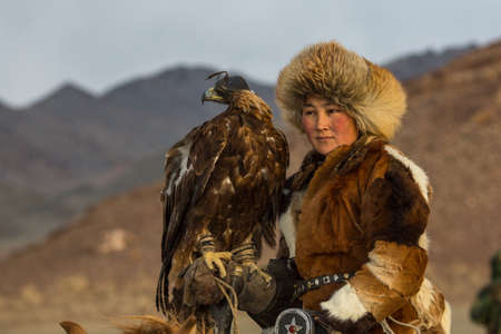 SAGSAY, MONGOLIA - SEP 28, 2017: Young woman Eagle Hunter at traditional clothing, while hunting to the hare holding a golden eagles on his arms in desert mountain of Western Mongolia.