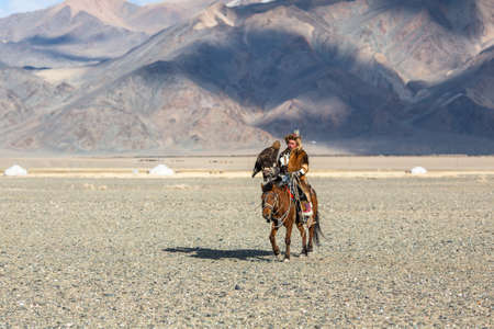 BAYAN-ULGIY, MONGOLIA - SEP 27, 2017: Kazakh Eagle Hunter at traditional clothing, on horseback while hunting to the hare holding a golden eagle on his arm in desert mountain of Western Mongolia.