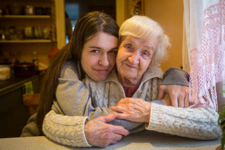 An elderly woman in an embrace with an adult granddaughter posing for the camera in a village house. Stock Photo