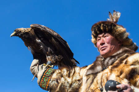 BAYAN-ULGII, MONGOLIA - SEP 30, 2017: Kazakh Eagle Hunter traditional clothing, while hunting to the hare holding a golden eagle on his arm in desert mountain of Western Mongolia. Redactioneel