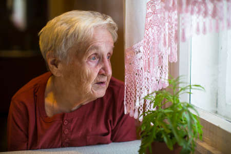 Older woman with longing looks out the window. Stock Photo