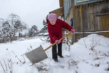 Elderly woman cleans the snow near his rural home. 写真素材