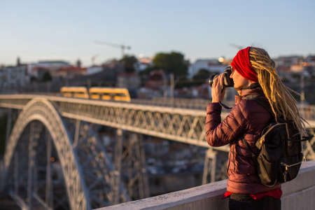 Young woman with dreadlocks on the viewing platform opposite the Dom Luis I bridge in Porto, Portugal.
