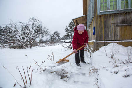 Elderly woman cleans the snow near home. Russia. Stock Photo