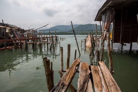 Broken abandoned pier of wooden planks in the Thai fishing village.