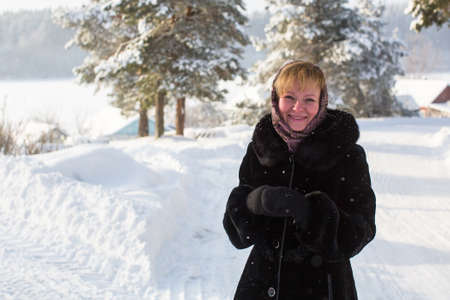 Young woman at winter in the snowy russian village. Banque d'images