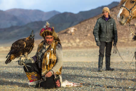SAGSAY, MONGOLIA - SEP 28, 2017: Berkutchi (Eagle Hunter) while hunting to the hare with a golden eagles on his arms in the mountains of Bayan-Olgii aimag. Stok Fotoğraf - 121227094