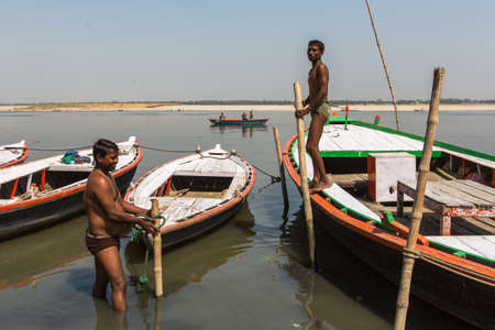 VARANASI, INDIA - MAR 13, 2018: Boatmen on the banks of Holy Ganga river. One of the oldest cities in the world, considered a Holy city for Buddhists and Jains, and as center of the Earth in Hindu cos