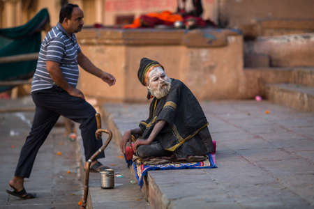 VARANASI, INDIA - MAR 21, 2018: Sadhu or Baba (holy man) on the ghats of Ganges river. Normally a sadhu is a monk, renounced, renounced material enjoyment. In India from 4 to 5 million sadhu.