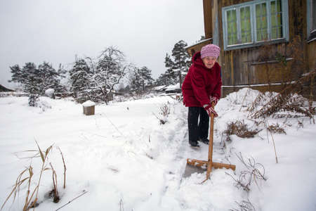 Elderly woman cleans the snow near rural home.