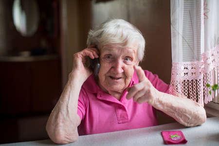 Een oudere vrouw praat emotioneel op een mobiele telefoon.