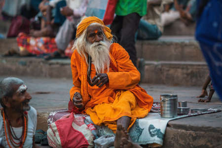 VARANASI, INDIA - MAR 29, 2018: Sadhu or Baba (holy man) on the ghats of Ganges river. Normally a sadhu is a monk, renounced, renounced material enjoyment. In India from 4 to 5 million sadhu. Editorial