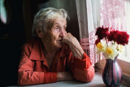 Starsza kobieta ze smutkiem wygląda przez okno. Zdjęcie Seryjne
