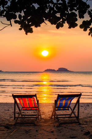 Loungers at the seaside at amazing sunset. Stock Photo