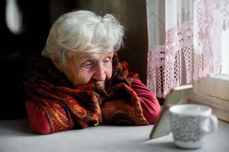 An elderly woman sitting at the table looking at the screen of the smartphone.