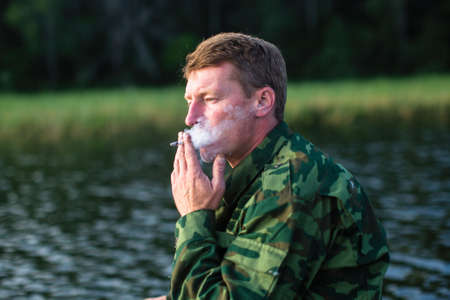 A man in camouflage smoking a cigarette outdoors.