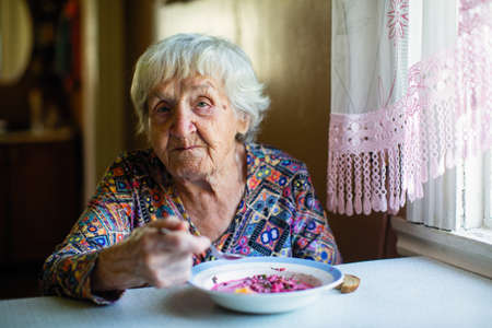 An elderly woman eating soup sitting at a table in the house. Stockfoto
