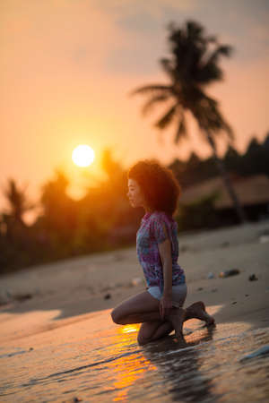 Young mixed race woman on a tropical beach during amazing sunset.