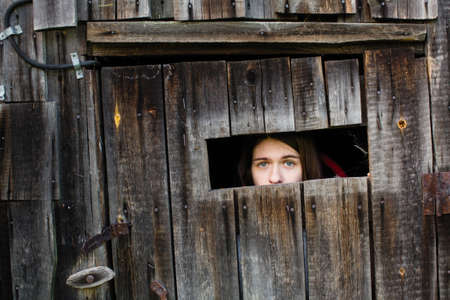 A young woman locked in a wooden old barn, sad looks out the slit.