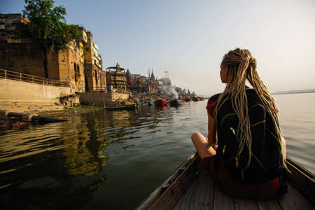 Woman traveler on a boat glides through the water on Ganges river along the shore of Varanasi, India.