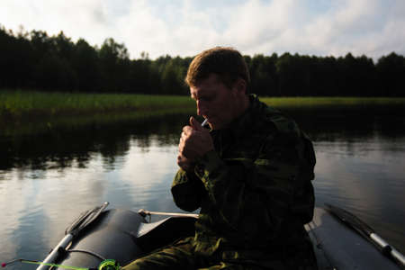 Man in an inflatable rubber boat on the lake lights a cigarette.