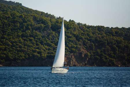 Sailing ships yacht glides through the waves near the Greek coast in the Aegean sea.