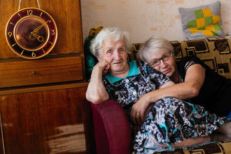 Elderly woman in his home with adult daughter. Banque d'images - 113969716