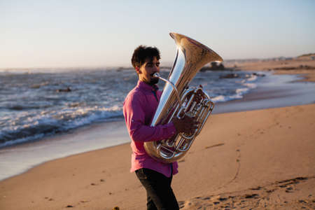 Young musician playing the tuba on the sea coast. Standard-Bild