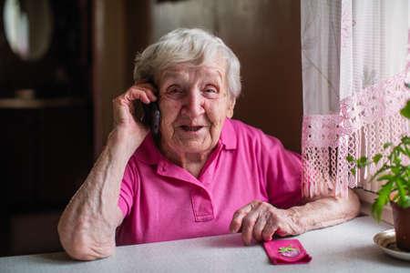 Mujer mayor anciana habla por un teléfono móvil. Foto de archivo