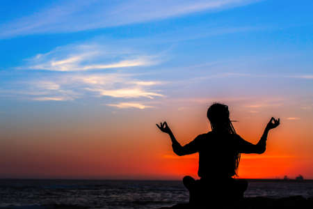 Yoga silhouette woman meditating in Lotus position on the ocean beach during amazing sunset.